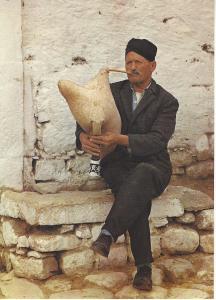 Greece Man playing goatskin bagpipe